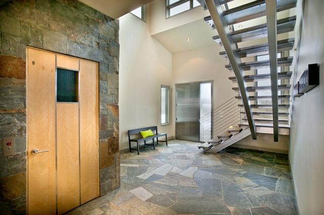 Acél lépcső és széles ajtajú felvonó