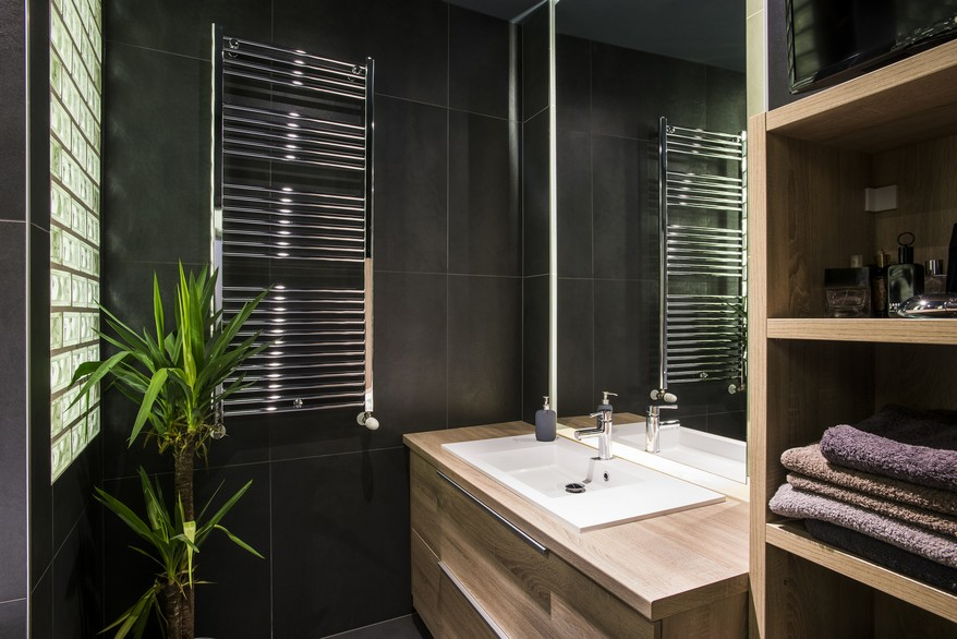 Férfias fürdőszoba sötétszürke lapokkal és natúr fa bútorokkal