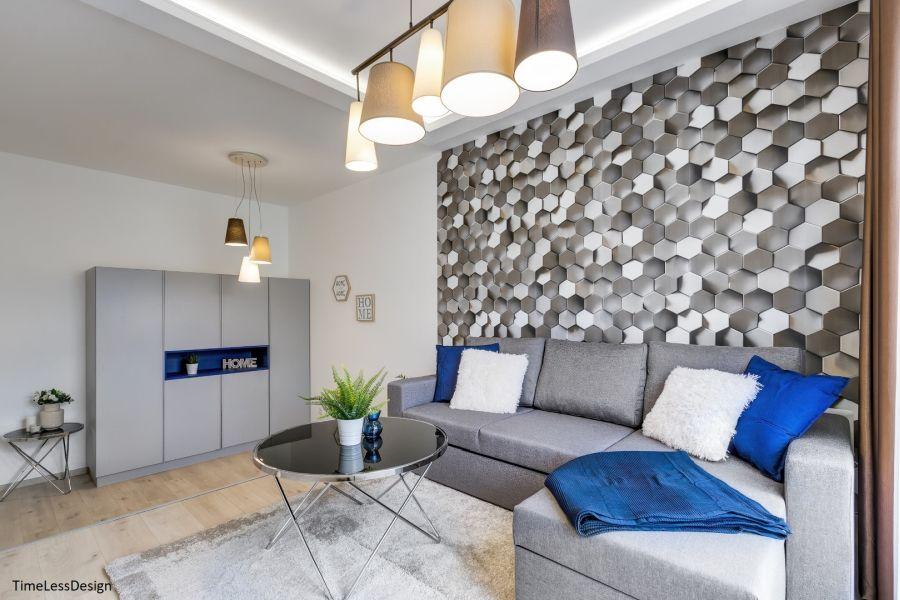 Hatszögletű csempe mintás tapéta és szürke sarokkanapé nappaliban
