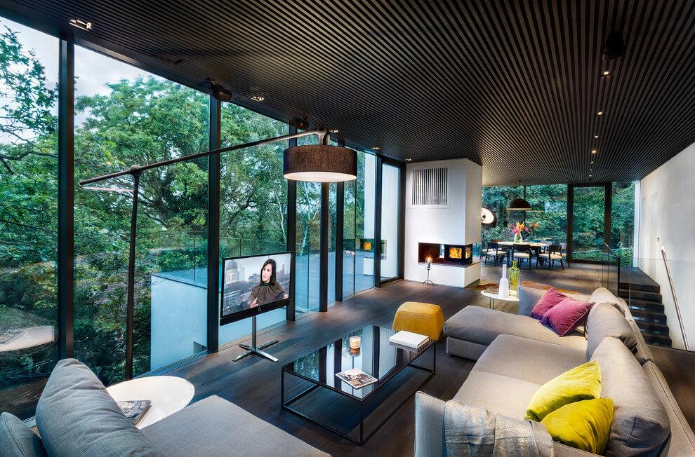 Színes nappali berendezés nagy üvegfalakkal övezve