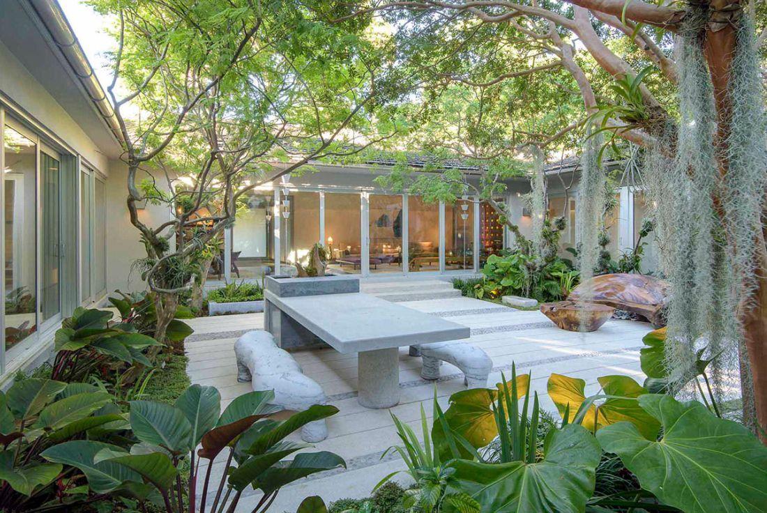 Buja zöld belső kert műkő kerti asztallal, csobogóval