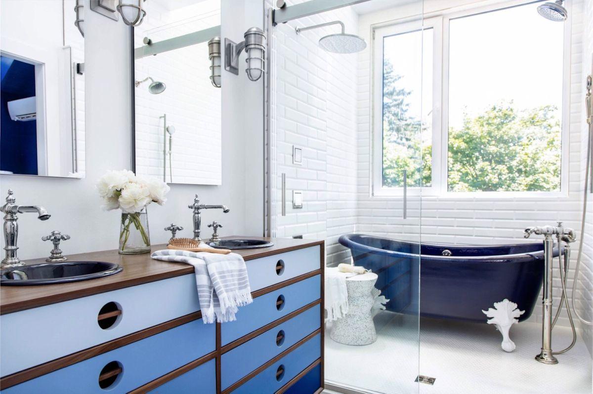 Kék lábas kád és ipari hangulatú fürdőszobai szekrény