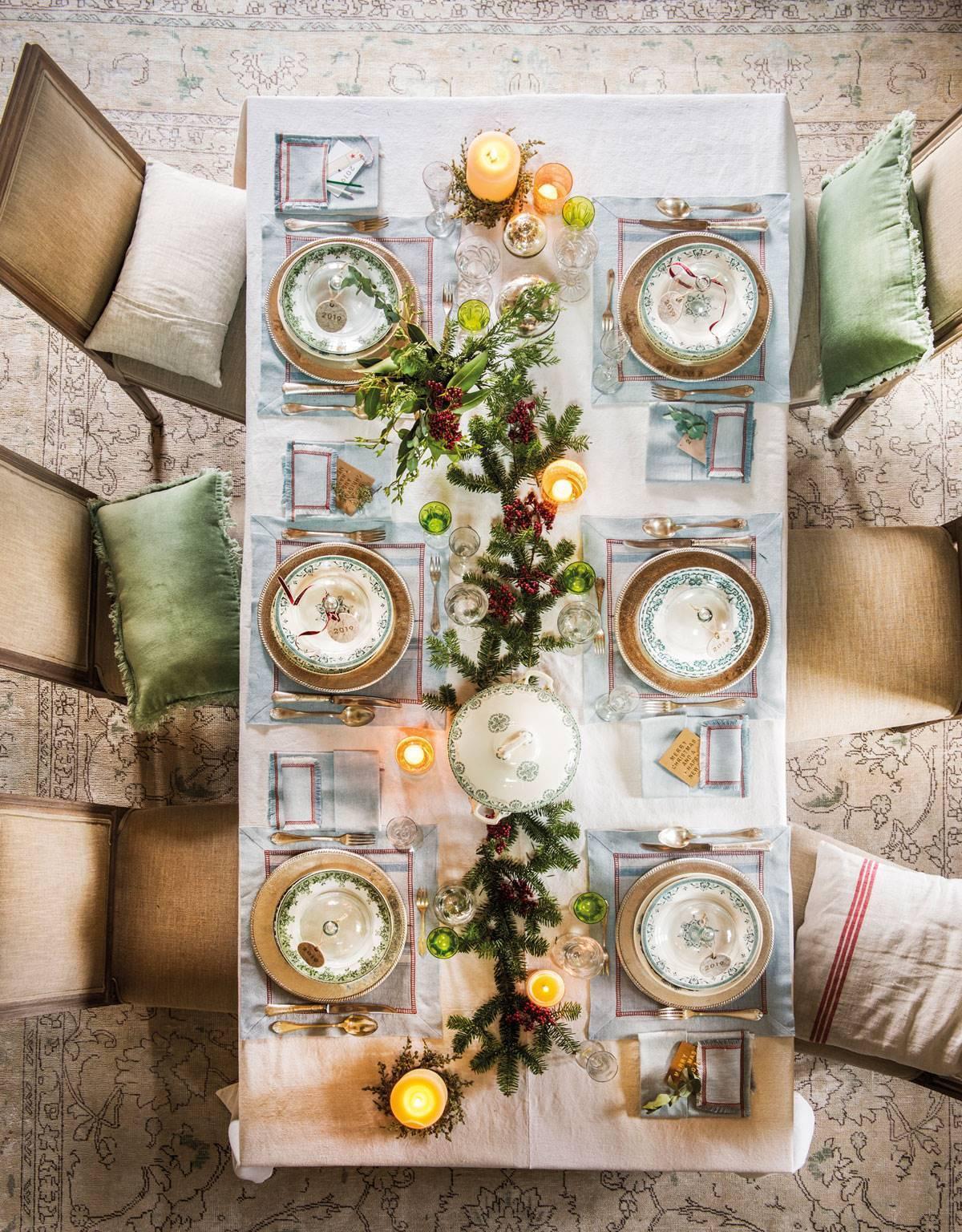 Fenyőágakkal díszített étkezőasztal és mázas kerámia étkészlet