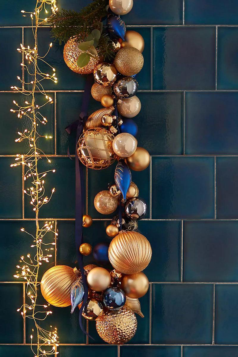 Sárga karácsonyfadísz kék falicsempe előtt