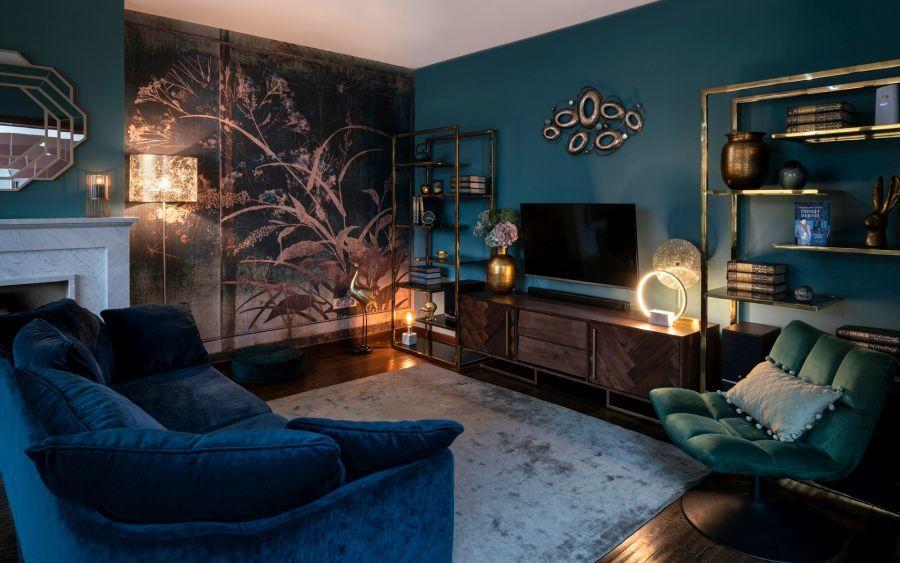 Az extravagáns tapéta adja meg a fókuszpontját ennek a sötét türkiz nappalinak