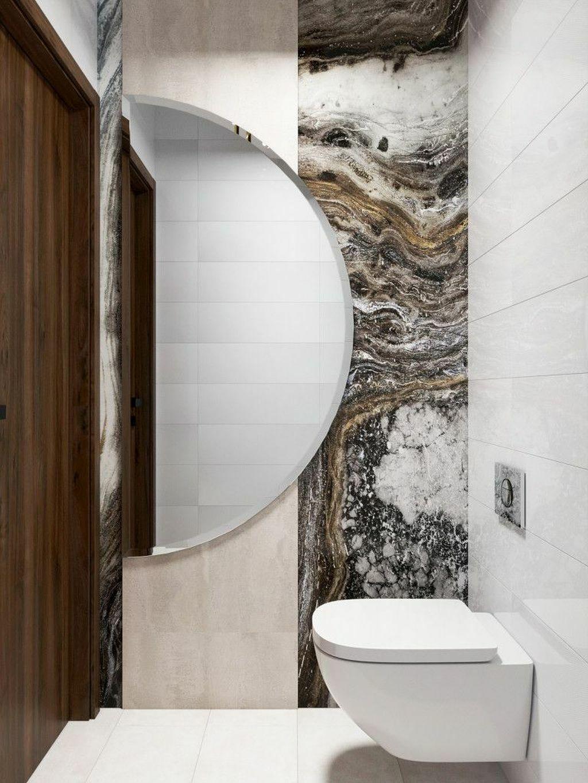 Nagy félkör alakú tükör a wc-ben a kőmintás falburkolat előtt
