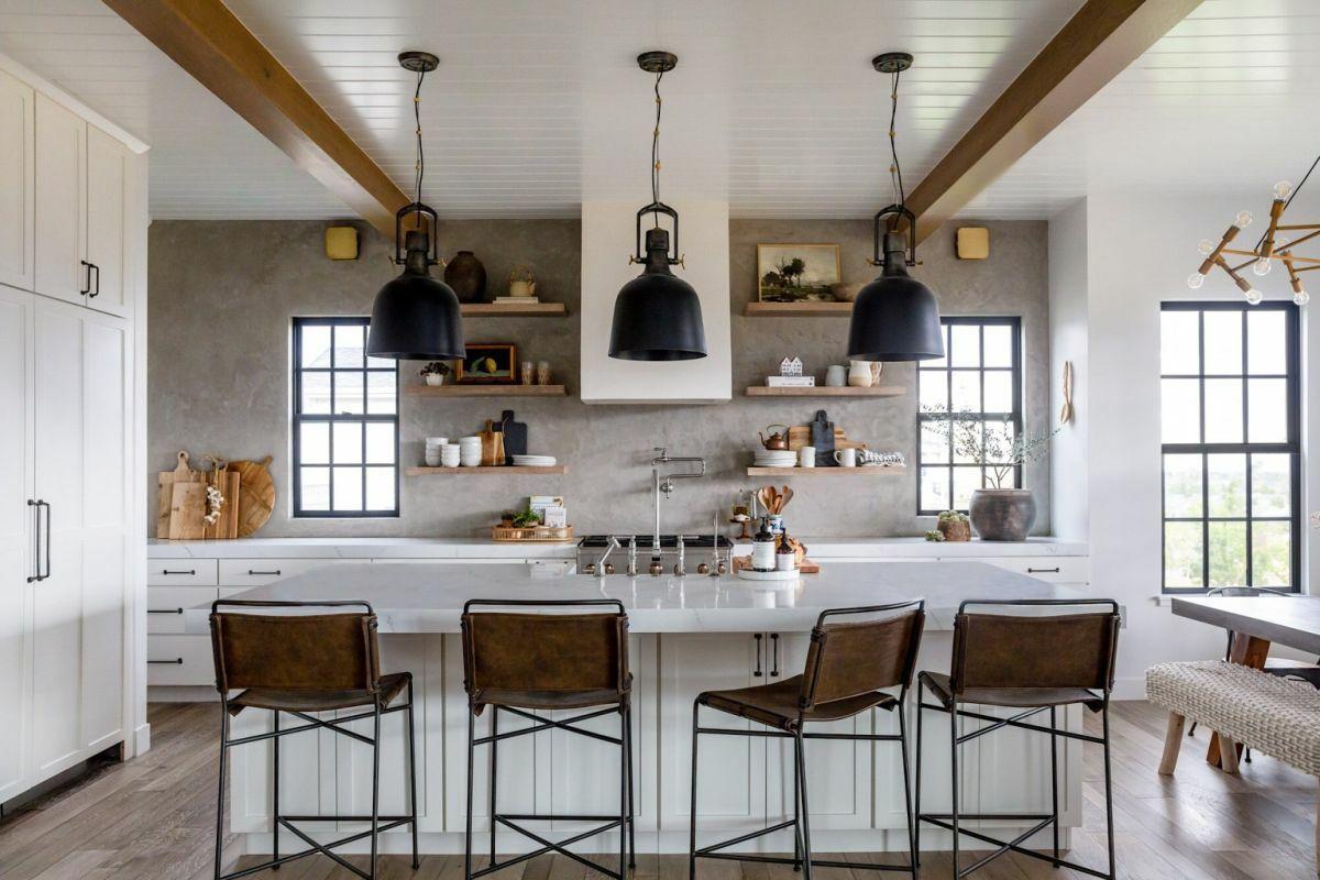 Szigetes konyha, előtte bőr bárszékek és karakteres fekete lámpák
