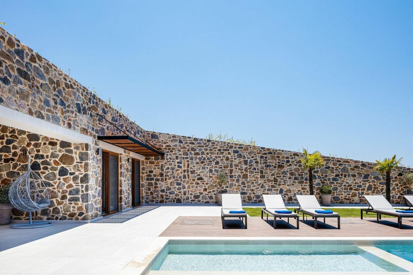 Dekoratív kőfalak adják a domboldalba épített ház homlokzatát