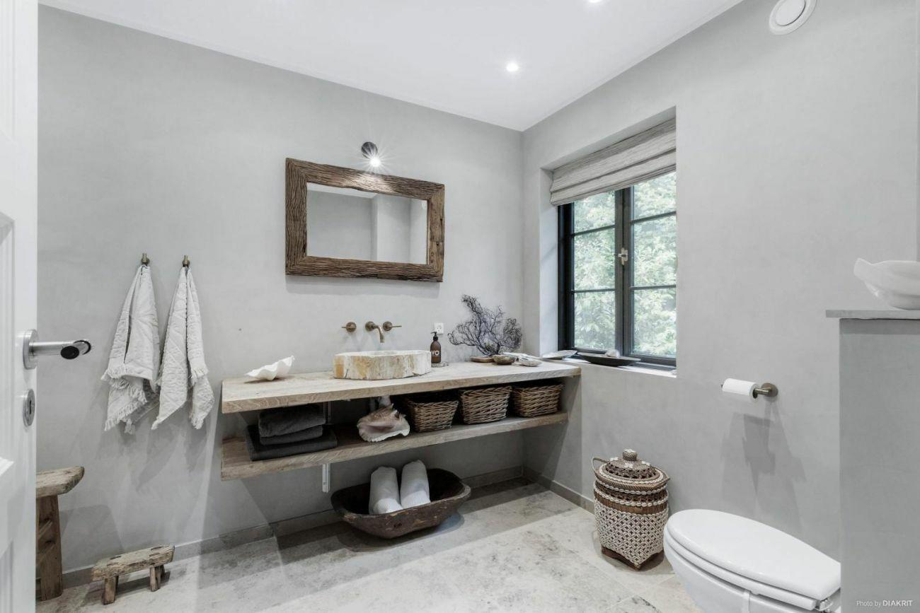 Visszafogott mosdópult tárolópolccal és ódon tükörkerettel