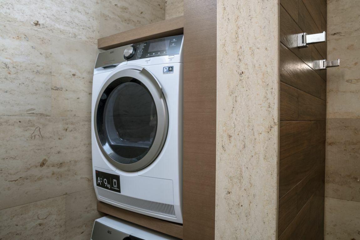 Egyedi asztalosmunkának köszönhetően a mosógép és a szárítógép is praktikusan tárolható